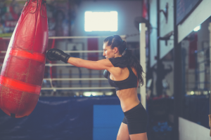 athletic female boxer punching red heavy bag