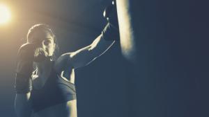 female boxer workout heavy bag